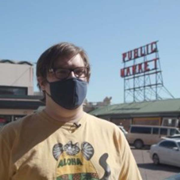 Tim wearing a mask a nd standing in front of the Public Market sign